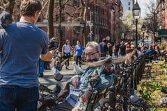 NEW YORK, ETATS-UNIS - 14 AVRIL 2018 : Pigeons de alimentation d'un homme plus âgé en parc près avec le village occidental à New  image stock