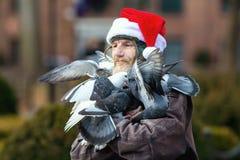 New York, Etats-Unis - décembre 2017, - homme sans abri dans le chapeau de Noël sur la rue avec des pigeons sur le corps Images stock