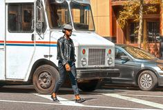20 05 2016 New York Etats-Unis, homme à la mode d'Afro-américain marchant au milieu du trafic sur la rue et musique de écoute ave photos stock