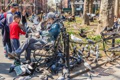 NEW YORK, EUA - 14 DE ABRIL DE 2018: Pombos de alimentação de um homem idoso em um parque próximo com a vila ocidental em New Yor imagens de stock royalty free