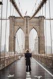 NEW YORK, EUA - 24 DE FEVEREIRO DE 2018: Turista que toma uma ruptura para contemplar a ponte de Brooklyn famosa para Manhattan d imagens de stock