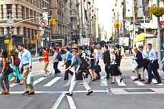 NEW YORK, EUA – 13 DE JULHO: Povos em um cruzamento pedestre em Manhattan do centro Imagens de Stock