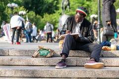 NEW YORK, EUA - 3 DE JUNHO DE 2018: Homem afro-americano que senta-se no desenho do parque Cena da rua de Manhattan Parque quadra fotos de stock royalty free