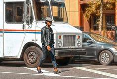 20 05 2016 New York EUA, homem afro-americano elegante que andam no meio do tráfego na rua e música de escuta com fotos de stock