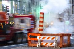 New York - February 6, 2013: street repairs with steam and rushing traffic royalty free stock image