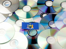 New York flag on top of CD and DVD pile isolated on white. New York flag on top of CD and DVD pile isolated Royalty Free Stock Image