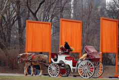 New York Gates And Carriage. Horse drawn carriage riding in front of Orange Gates in New York's Central Park Stock Photos