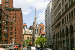 New York - Grace Church. New York City, USA - May 19, 2014: The Grace Church in Lower Manhattan in the middle of high buildings Stock Photo