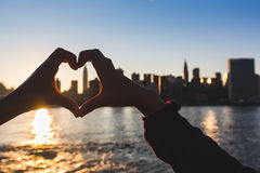 New York. Heart Shaped Hands at Sunset,New York Skyline on Background royalty free stock photography
