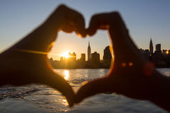 New York. Heart Shaped Hands at Sunset, New York Skyline on Background stock photography