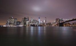 New York horisont och Brooklyn bro vid natt Fotografering för Bildbyråer