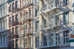 New York houses facades with fire escape stairs background Stock Photos