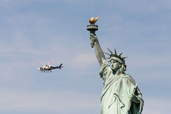 NYPD helicopter near Statue of Liberty, USA Stock Image
