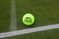 Slazenger Wimbledon Tennis Ball on grass tennis court. NEW YORK - JULY 2, 2019: Slazenger Wimbledon Tennis Ball on grass tennis court. Slazenger Wimbledon Tennis royalty free stock photo