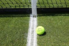 Slazenger Wimbledon Tennis Ball on grass tennis court. NEW YORK - JUNE 26, 2018: Slazenger Wimbledon Tennis Ball on grass tennis court. Slazenger Wimbledon royalty free stock images