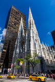 New York, Manhattan. ​NEW YORK - SEPTEMBER 19: View to the St. Patricks Cathedral in Midtown Manhattan with the famous 5th Avenue on SEPTEMBER 19, 2015. Its a Stock Photos
