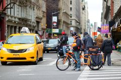 NEW YORK - MARCH 16, 2015: Cyclist and taxi cabs rushing on busy streets of downtown Manhattan. stock photo