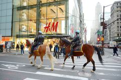 NEW YORK - MARCH 16, 2015: Police officers ride their horses downtown in New York on East 48th street, Manhattan. USA royalty free stock images