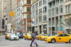 NEW YORK - MARCH 16, 2015: Yellow taxi cabs and people rushing on busy streets of downtown Manhattan. stock photography