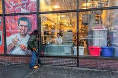 NEW YORK, NEW YORK - 10. JANUAR 2014: Unknow-Person, die durch das Fenster zum Lebensmittel-Hersteller schaut Restaurant Stockfotografie