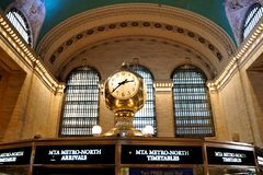 Interior of Main Concourse of Grand Central Terminal with the Clock and people walking around. Beautiful windows, zodiac ceiling. royalty free stock image