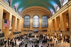 Interior of Main Concourse of Grand Central Terminal with zodiac ceiling, the Clock and people walking by. stock image