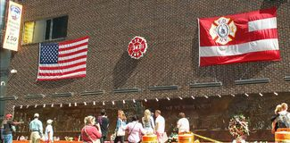 NEW YORK, NEW YORK, USA - SEPTEMBER 15, 2015: flags on a wall at a memorial to ny fire fighters killed on sept 11 royalty free stock photos