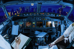 New York night flight. Night flight inside a cockpit flying on New York skyline of United States of America.. Pilots arms and blank white papers for copy space Stock Images