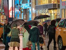 Times Square tourists walk past retail stores on a rainy day holding umbrellas stock image