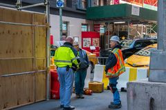New York, NY - April 3, 2019: Group of three construction workers in reflective vests and hard hats at a construction site on a royalty free stock photo