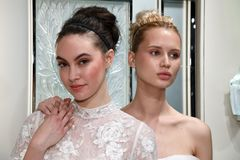Models Heather Aboff L and Milena Garbo R presenting dresses during the Gracy Accad Spring 2020 bridal presentation. NEW YORK, NY - APRIL 10: Models Heather stock photos