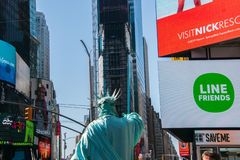 Back of the Statue of Liberty character with the buildings seen in Times Square in the background royalty free stock photo