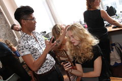 NEW YORK, NY - June 16: A hair stylist getting model ready backstage Stock Images
