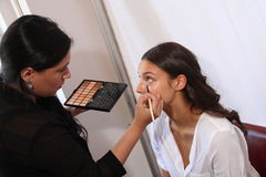 NEW YORK, NY - June 16: A makeup artist applying makeup to model face backstage Stock Photo