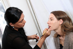 NEW YORK, NY - June 16: A makeup artist applying makeup to model face backstage Royalty Free Stock Photography