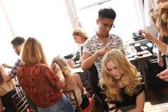 NEW YORK NY - Juni 16: En hårstylist som får modell klart i kulisserna Arkivbilder