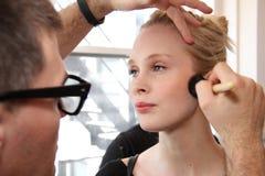 NEW YORK NY - Juni 16: En makeupkonstnär som i kulisserna applicerar makeup till modellframsidan Arkivfoto