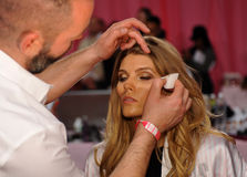 NEW YORK, NY - NOVEMBER 13: Makeup Artist Dick Page applying make-up to Maryna Linchuk at the 2013 Victoria's Secret Fashion Show Royalty Free Stock Image