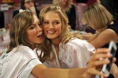 NEW YORK, NY - NOVEMBER 13: Models Karlie Kloss ( L) Toni Garrn (R) making faces for phone snapshots backstage Royalty Free Stock Photography