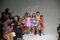 NEW YORK, NY - OCTOBER 19: Designer Peini Yang (C) walks the runway with models during the Aria Children's Clothing preview at pet Royalty Free Stock Images