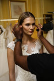 NEW YORK, NY - OCTOBER 09: A model getting ready backstage wearing Oleg Cassini Fall 2015 Bridal collection. At the Plaza Athenee on October 09, 2014 in New royalty free stock photo