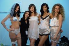 NEW YORK, NY - OCTOBER 25: Models and designer Maggie Gillette (in black) pose backstage during The Giving Bride Spring 2015 Stock Photo