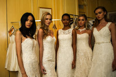NEW YORK, NY - OCTOBER 09: Models posing backstage wearing Oleg Cassini Fall 2015 Bridal collection. At the Plaza Athenee on October 09, 2014 in New York City stock photo