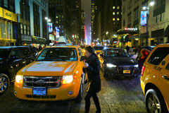 New York. NY, USA - January 25, 2013: A woman cross the 34th Street between cars and yellow cabs, at snowing night. This Winter was the most cold of the last Stock Images