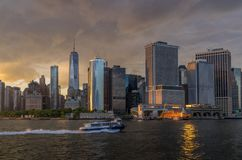 View of NYC skyline at sunset. New York, NY. USA - JUNE 4, 2018. Panorama view of  NYC Lower Manhattan skyline with sailboat passing by in New York Harbor Royalty Free Stock Images