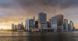 View of NYC skyline at sunset. New York, NY. USA - JUNE 4, 2018. Panorama view of  NYC Lower Manhattan skyline with sailboat passing by in New York Harbor Stock Photography