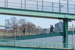 New York, NY/USA - 3/19/2019: La gente che cammina pareggiare lungo una struttura d'acciaio accanto al East River, con fotografia stock libera da diritti