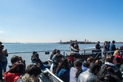 New York, NY / USA - March 2016: People on a cruise tour to Ellis Island and Statue of Liberty in early spring Royalty Free Stock Photos
