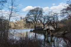 New York, NY / USA - March 2016: a view on the pond and a wooden arbor in the Central Park, blue sky and bare trees. Spring landscape Royalty Free Stock Image