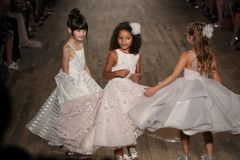 Kid models walk the runway for Blush by Hayley Paige  Bridal show Fall/Winter 2018 Collection. NEW YORK - OCTOBER 6: Kid models walk the runway for Blush by Royalty Free Stock Images